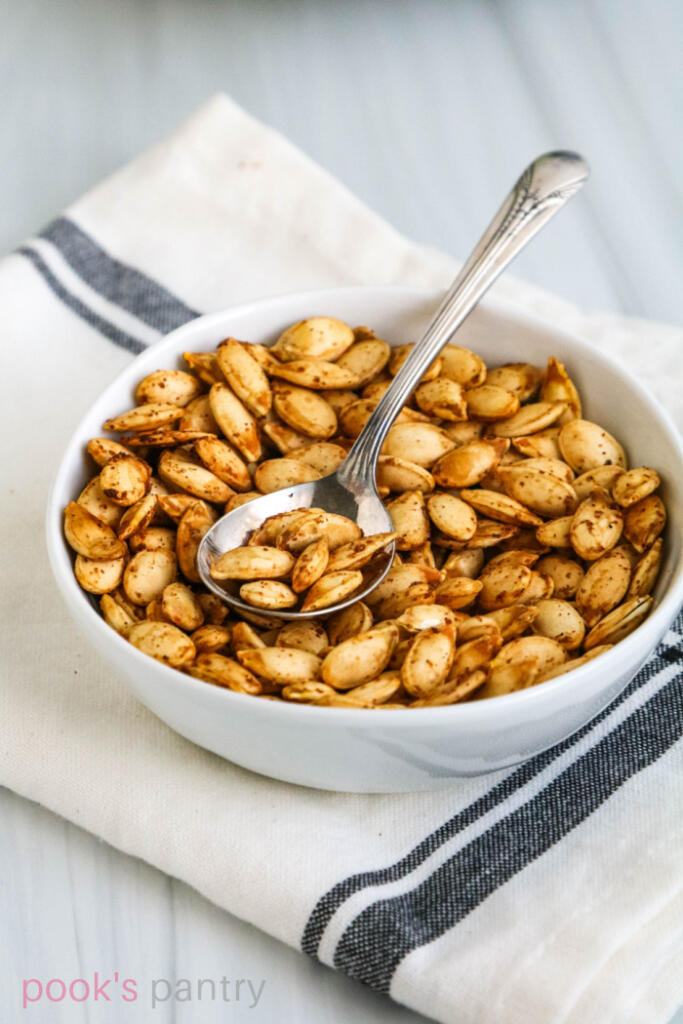 Toasted Hubbard seeds in small white bowl on striped kitchen towel.