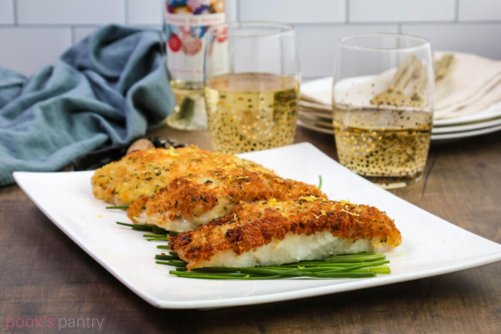 Panko crusted corvina on a bed on chives with wine bottle and glasses in background.
