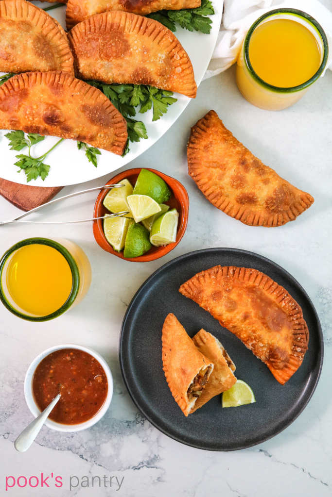 Cuban beef empanadas on a black plate with a wedge of lime.