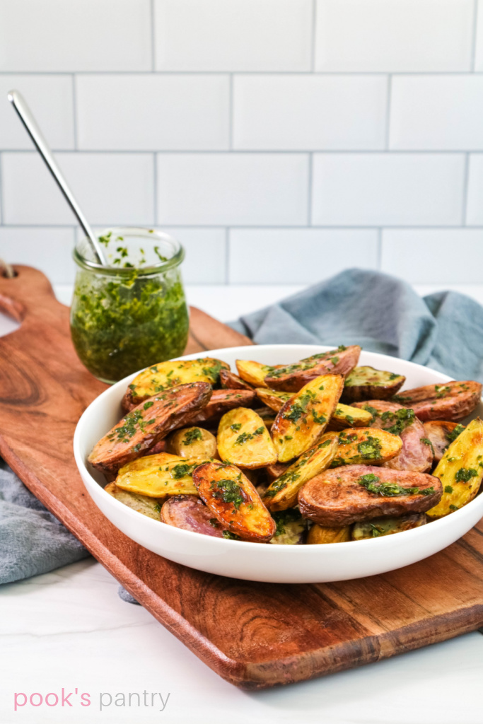 Roast fingerling potatoes with gremolata sauce in white bowl.
