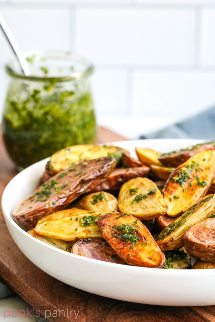 Gremolata fingerling potatoes on white bowl on wooden cutting board.