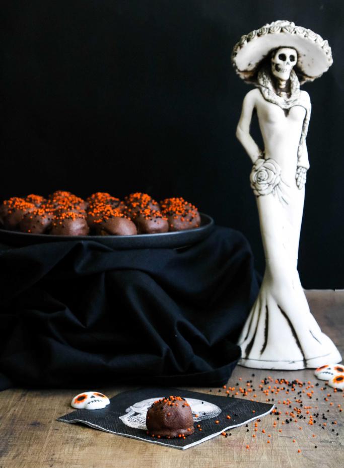 Halloween rum balls on black plate with one rum ball on skull napkin.