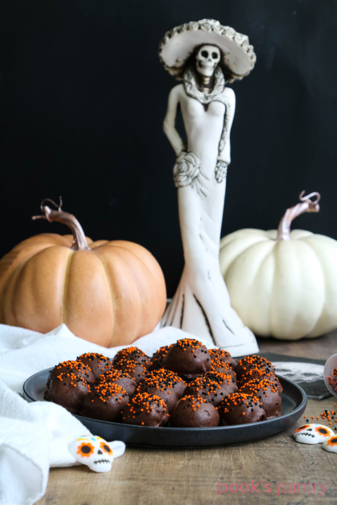 Rum balls for Halloween on black plate with pumpkins in background.