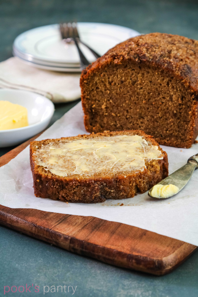 Hubbard squash bread with butter on wooden board.