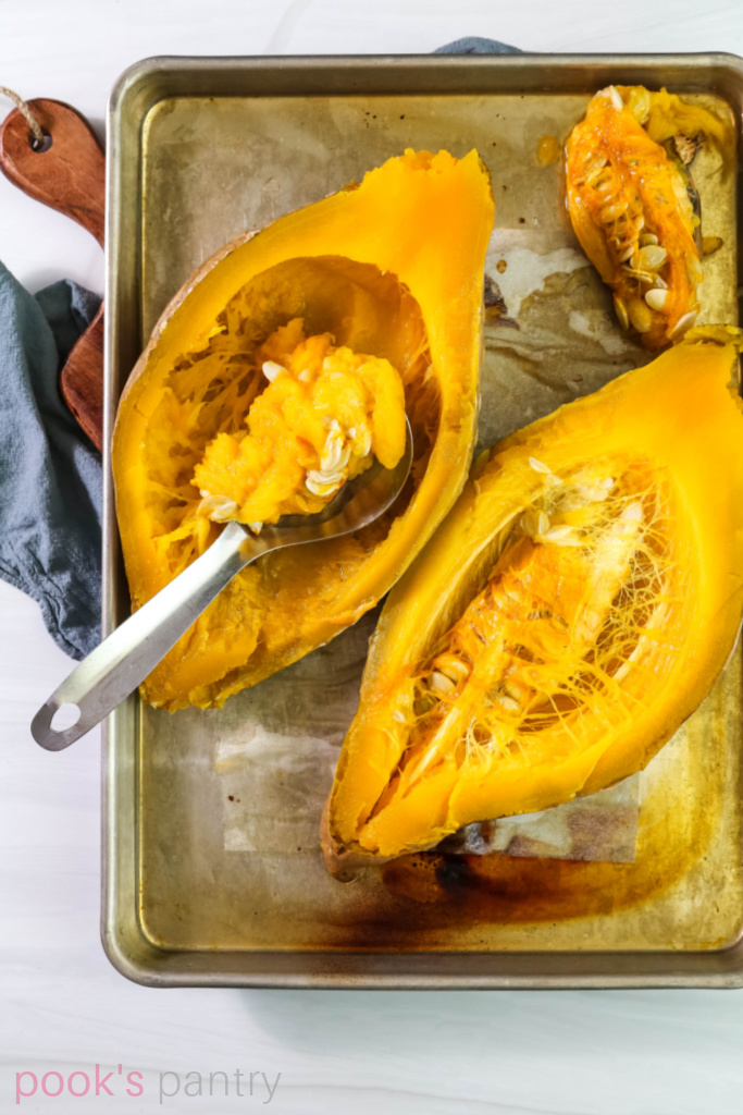 Scooping seeds from whole cooked squash.
