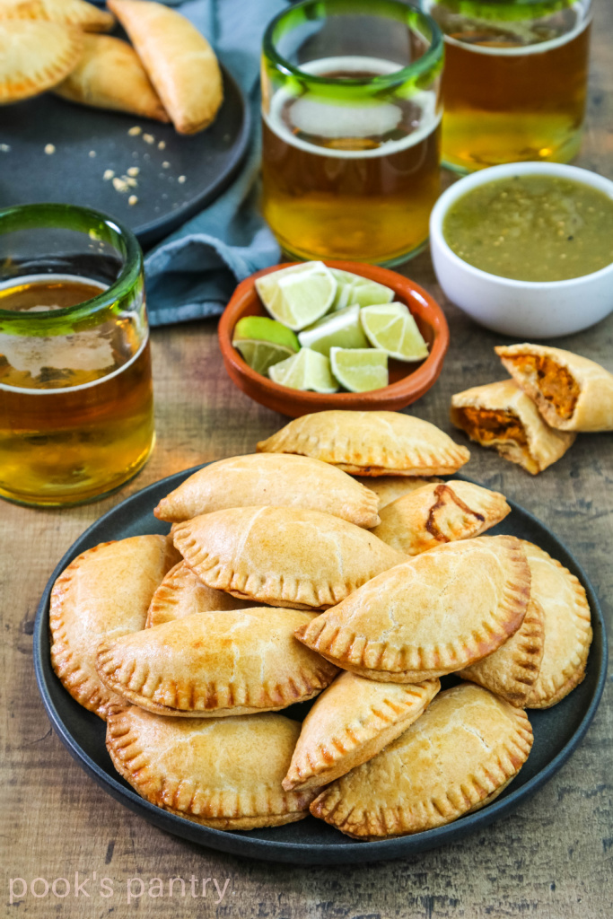 Plate of baked pumpkin empanadas with beer and limes in the background.